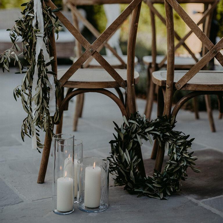 Kranz und Kerzen vor Holzstühlen
