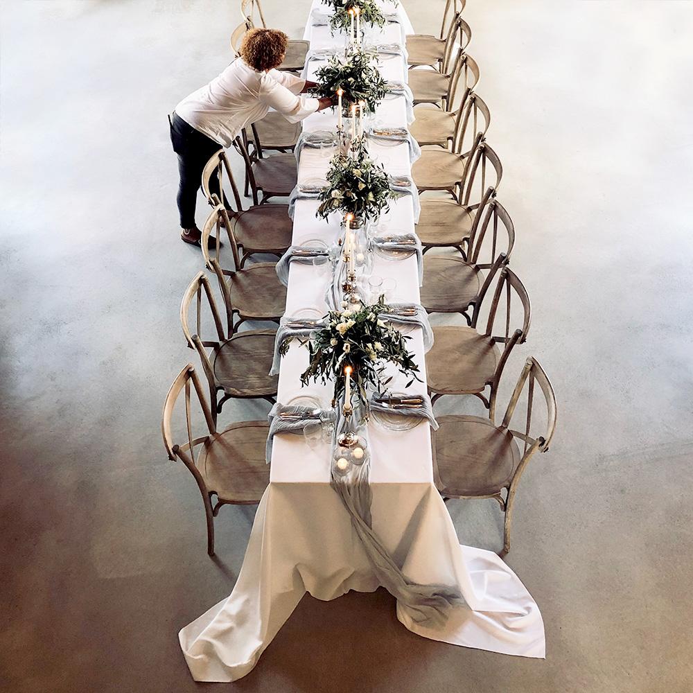 Fru Lehmann dekoriert eine lange Tafel mit Kerzen und Blumengestecken